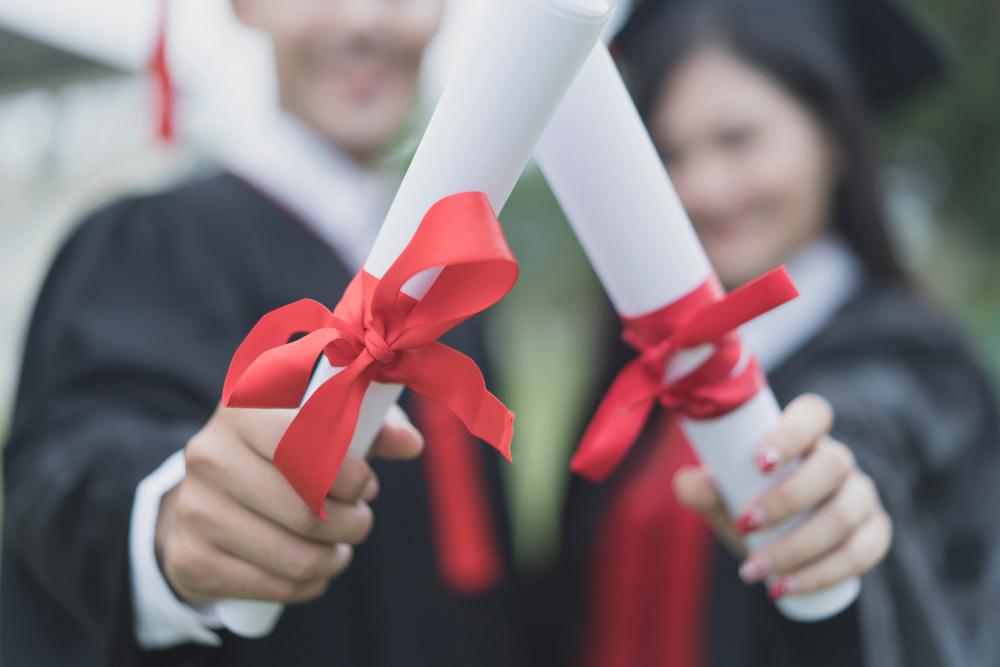 Alunos segurando diplomas de segunda graduação