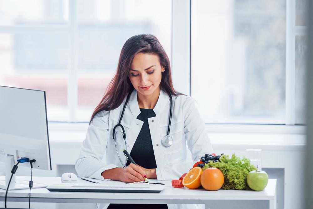 Mulher nutricionista em consultório, no exercício da profissão