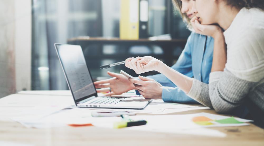 Profissionais de Marketing Digital discutindo estratégias e fazendo brainstorm