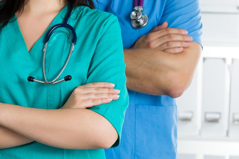 Dois profissionais da área da saúde de braços cruzados