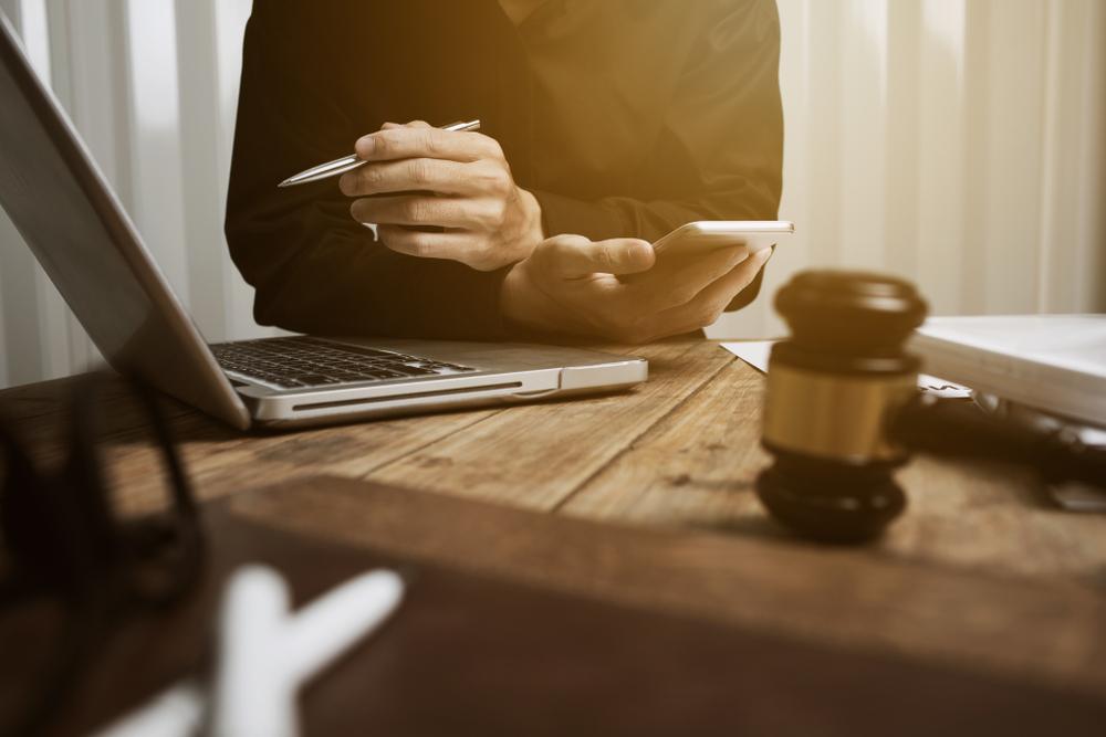 Estudante da faculdade de Direito com caneta em uma mão, celular na outra e em frente a um laptop